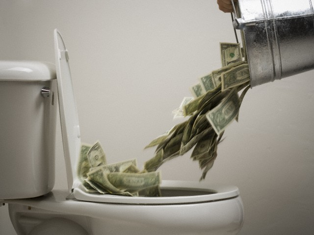 Person dumping money into a toilet bowl